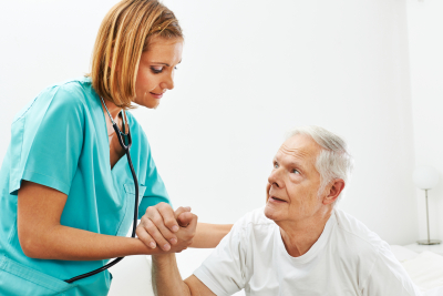 nurse holding the hand of the elder man