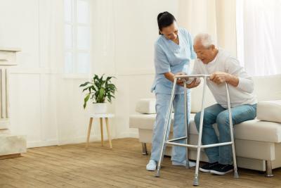 nurse assiting the elder man as he walks
